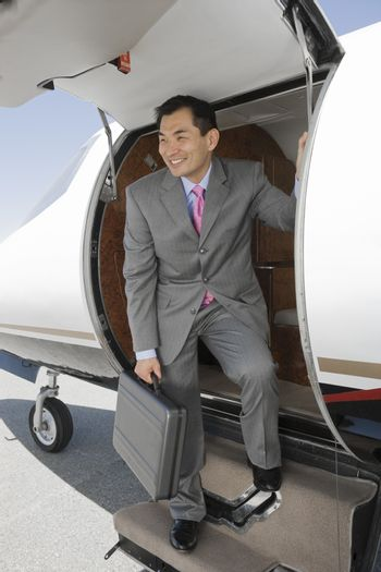 Successful Japanese businessman standing on ladder of private airplane at airfield