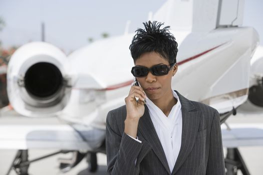 Confident businesswoman using cell phone with airplane in the background at airfield