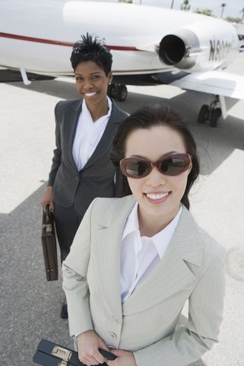 Portrait of a successful businesswoman with colleague with airplane in the background at airfield