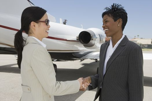 Two business women shaking hands with airplane in the background at airfield