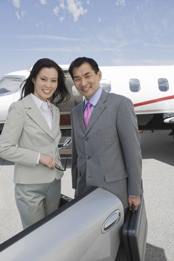 Portrait of two multiethnic business colleagues standing together by vehicle at airfield