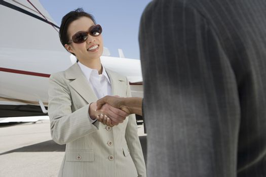 Two happy multiethnic business women shaking hands with airplane in the background at airfield