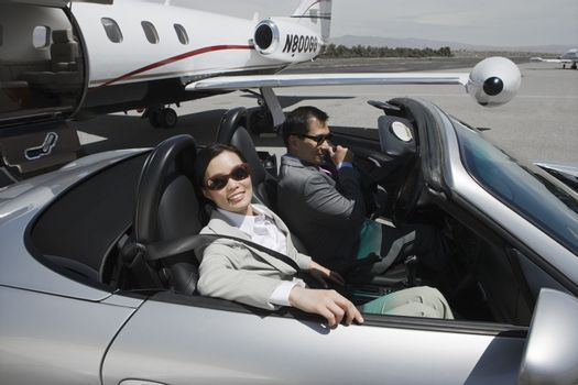 Portrait of Korean businesswoman sitting in car with businessman at airfield