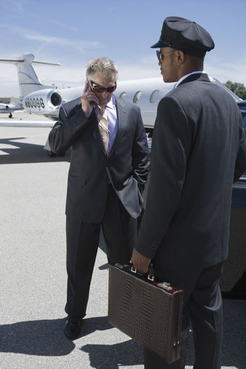 Serious businessman using cellphone with car driver holding briefcase at airfield