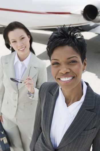 Portrait of two multiethnic business colleagues at the airfield