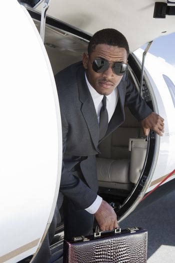 An African American businessman getting down from airplane at airfield