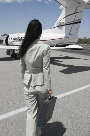 Rear view of businesswoman walking towards private airplane at airfield