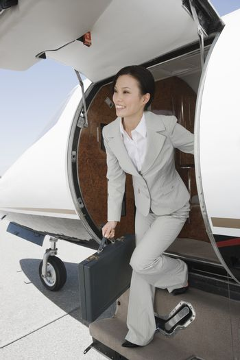 Happy Korean business woman getting down from private airplane at airfield
