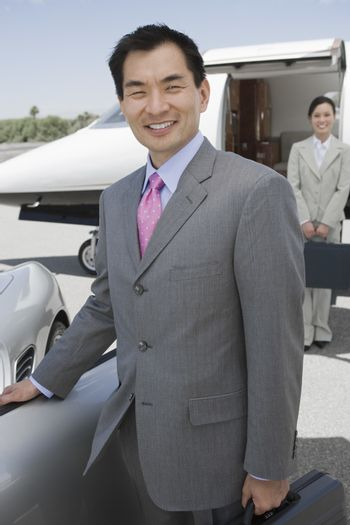 Portrait of happy businessman standing with colleague in the background at airfield