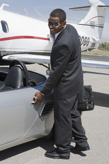 An African American businessman opening the door of car at airfield