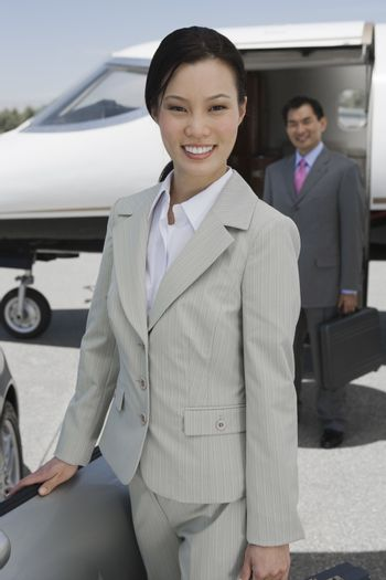 Portrait of happy businesswoman standing with colleague in the background at airfield