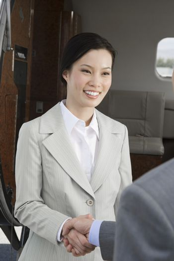 Korean business woman shaking hand with business man at airfield