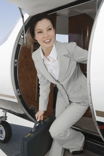 Happy Korean businesswoman getting down from airplane at airfield