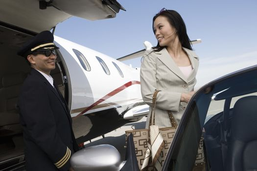Business woman looking at airplane pilot while standing by car at airfield