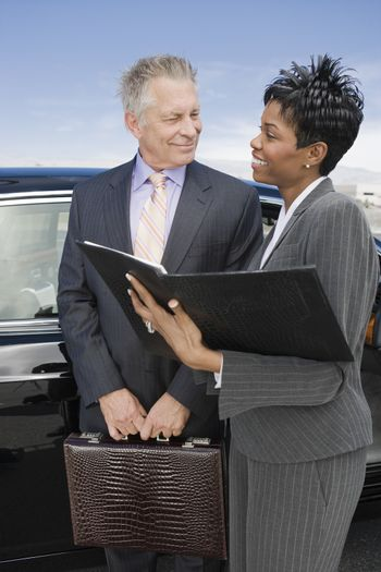 Two happy business people discussing the reports standing by car at airfield