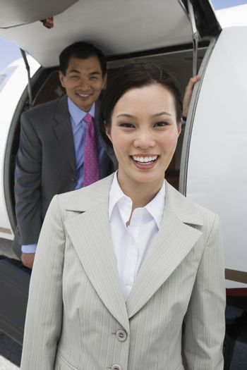 Portrait of two happy multiethnic business people standing by airplane at airfield