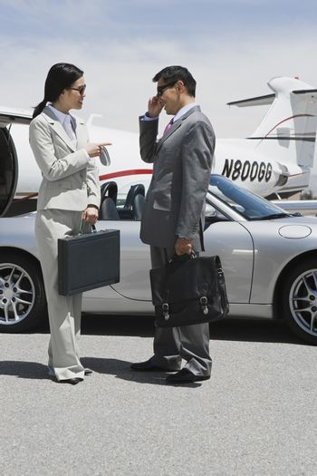 Full length of two business people communicating at airfield