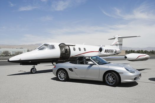 Convertible and private jet on landing strip.