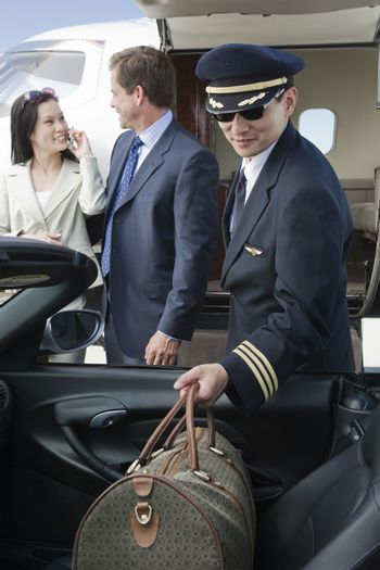 Airplane pilot keeping luggage in car with business people in the background at airfield