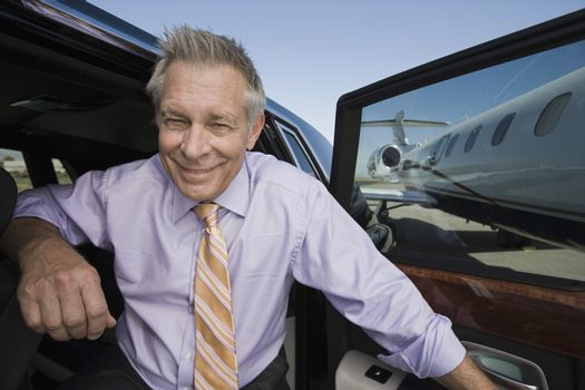 Portrait of a happy senior businessman getting down from car at airfield
