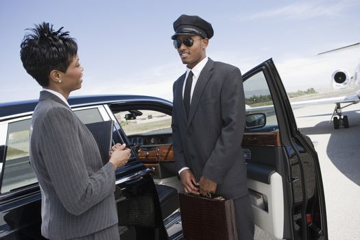 An African American business woman communicating with driver while standing by car on airfield