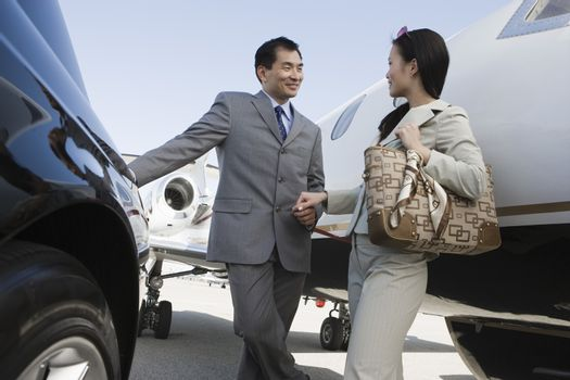Japanese businessman and Korean businesswoman holding hands at airfield