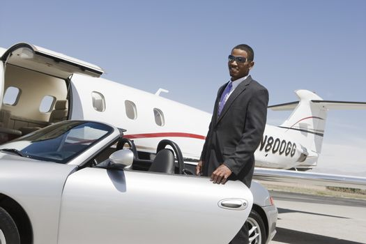 An African American businessman standing by car with airplane in the background at airfield