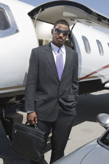 Smart African American businessman standing with attitude at airfield