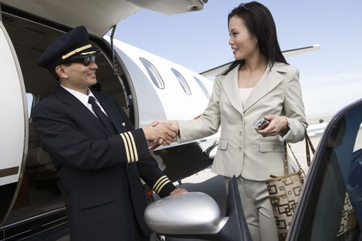 Korean businesswoman shaking hand with Japanese pilot at airfield
