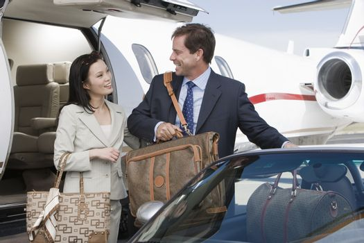 Businesswoman and businessman getting in a car with luggage at airfield