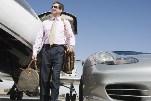 Low angle view of happy mature businessman standing with luggage on airfield