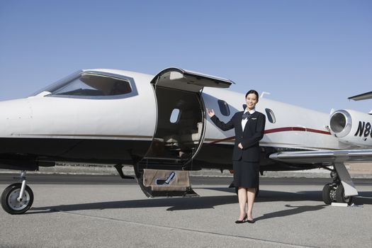 Portrait of beautiful stewardess standing by airplane at airfield