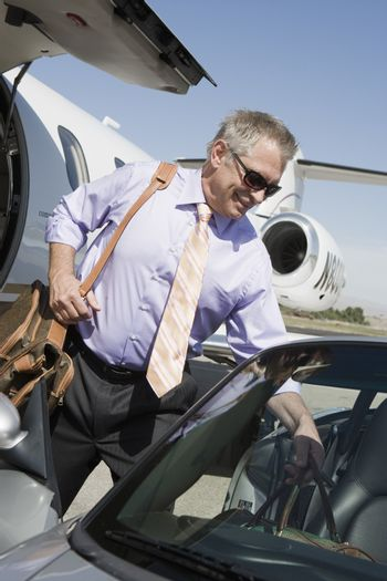 Senior businessman keeping luggage in car with airplane in the background at airfield