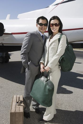 Full length of business couple standing together with luggage at airfield