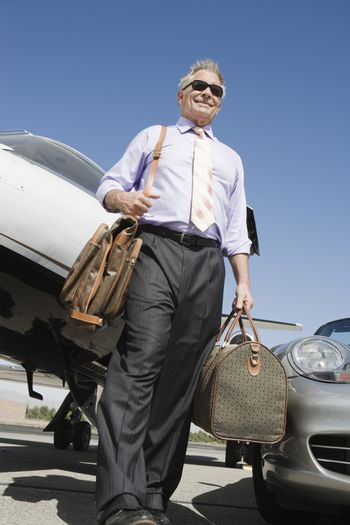 Low angle view of senior businessman walking with luggage on airfield