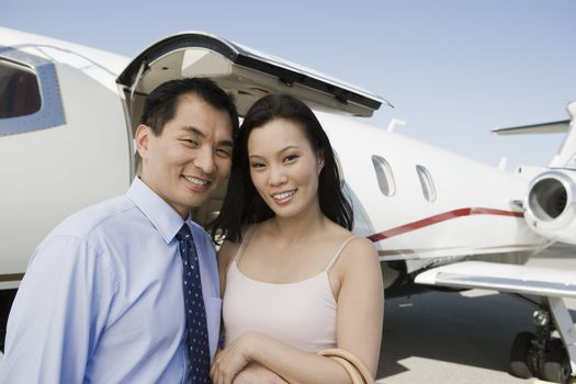 Portrait of happy business couple with airplane in the background at airfield