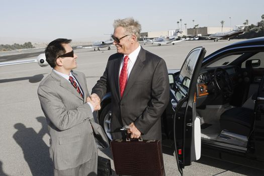 Two successful businessmen shaking hands while standing by car at airfield