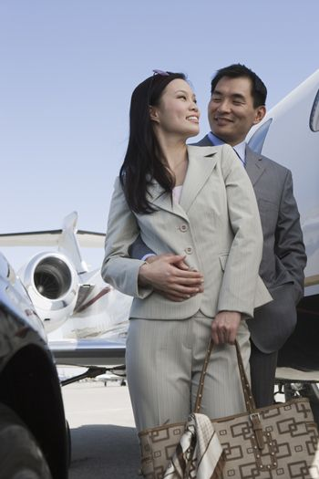 Loving business couple standing together on airfield