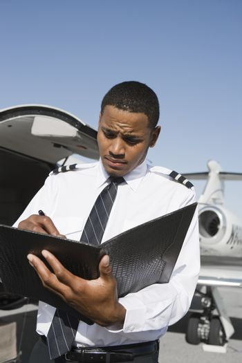 An airplane pilot taking notes on notepad with airplane in the background at airfield