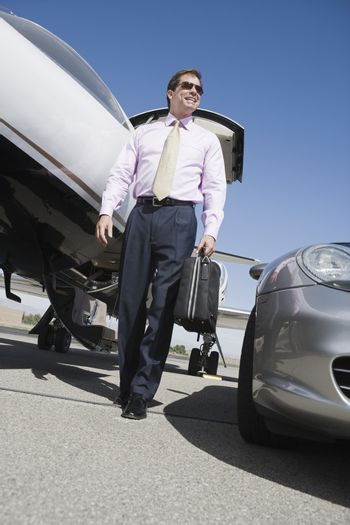 Low angle view of mature businessman walking with briefcase on airfield