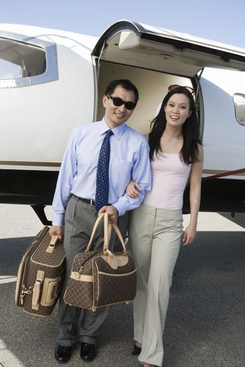 Portrait of an Asian business couple standing together with airplane in the background at airfield