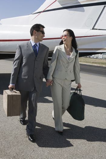 Full length of business couple walking together with luggage at airfield