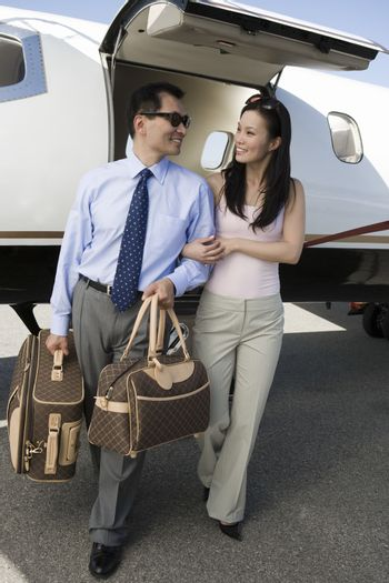 Full length of happy business couple walking together with airplane in the background at airfield