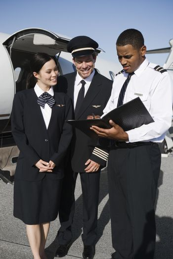 Multiethnic Cabin crew members discussing reports with airplane in the background at airfield