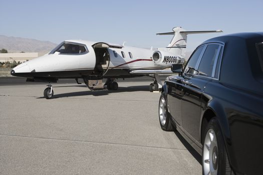 Luxurious black car with private airplane at airfield