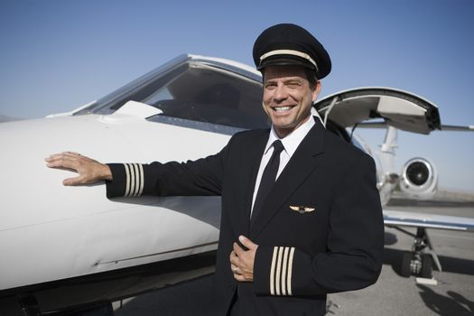 Portrait of happy airplane captain standing by aircraft at airfield