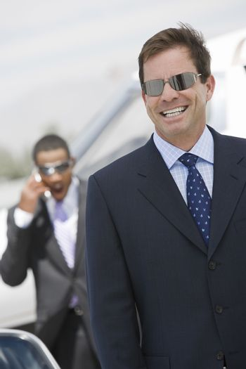 Mature businessman smiling with colleague using cell phone in the background at airfield