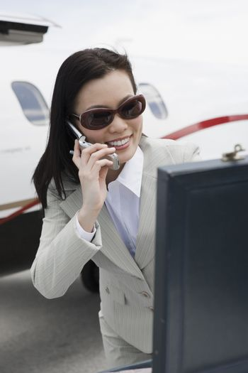 Happy Asian Korean businesswoman on a call at airfield