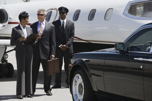 Business people discussing reports with driver in the background at airfield