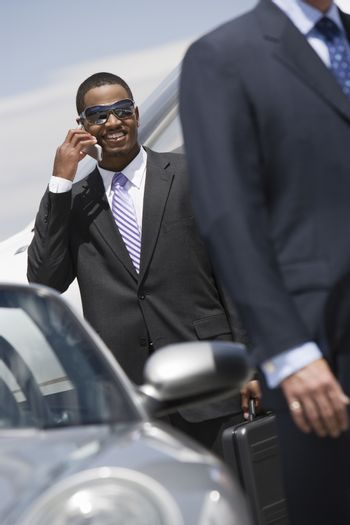 Young African American businessman on a call standing by car at airfield